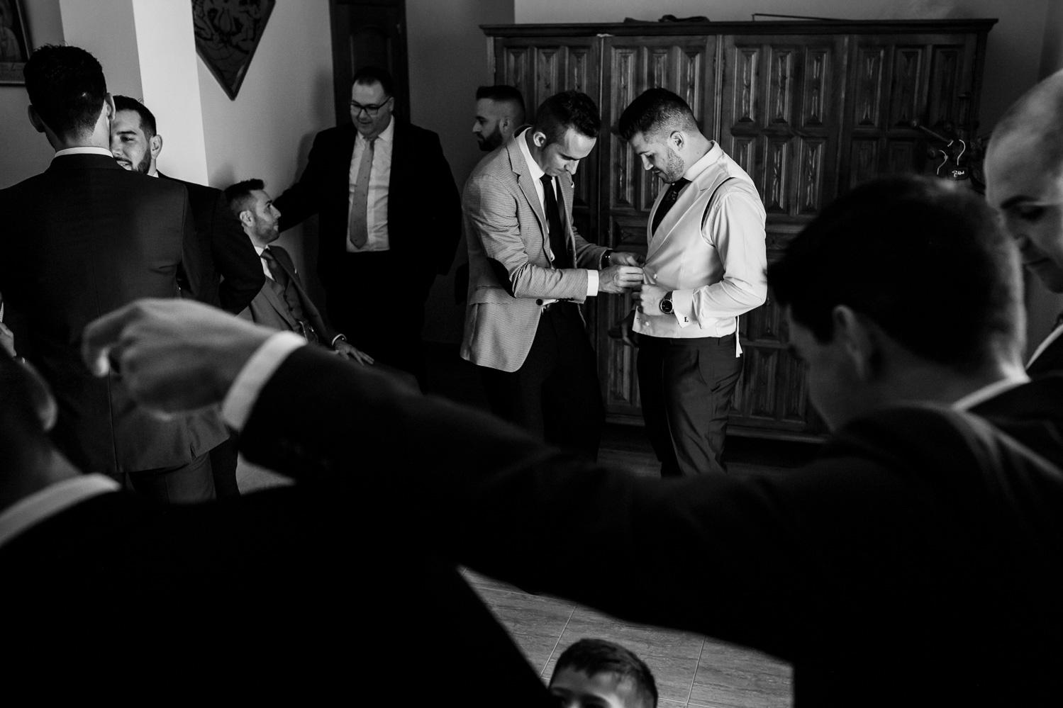 amigos ayudando al novio en su habitación en blanco y negro